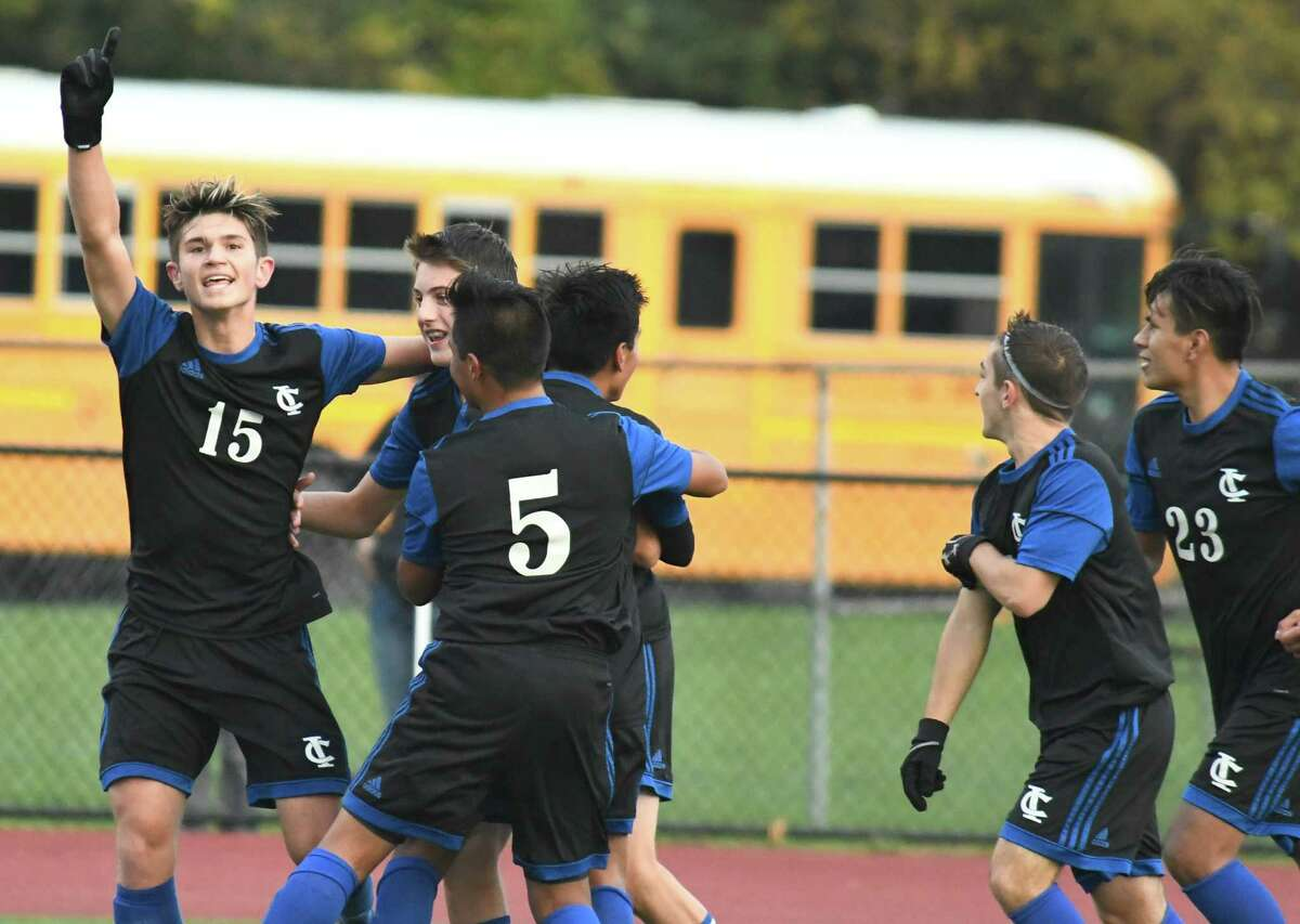 Ichabod Crane's Logan Groat (15) signals number one to the audience after his teammate, Joe Dolan, in the huddle (19), scored a goal against Schuylerville during the Class B sectional boys soccer semifinals in Mohonasen, N.Y., on Tuesday, Oct. 23, 2018. (Jenn March, Special to the Times Union )