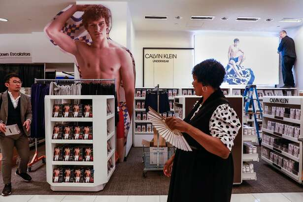 Grant Wright (right) works on a display in the Men's section of Macy's in San Francisco, California, on Tuesday, Oct. 16, 2018.