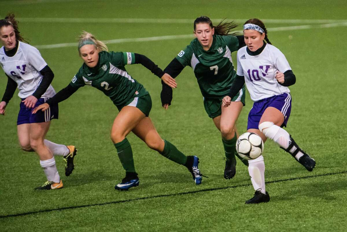 Voorheesville's Kaelyn Lawson kicks the ball past Schalmont's Makenzie Tripp and Brooke Galka as the class b girls' soccer semifinals were held at Lansingburgh High School in Troy, NY Tuesday, October 23rd, 2018. Photo by Eric Jenks for the Times Union