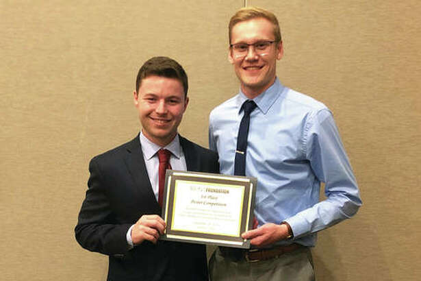 SIUE student researchers Brentsen Wolf, left, and Gregory Takacs earned first place for scientific merit at the Illinois Pharmacists Association September meeting.