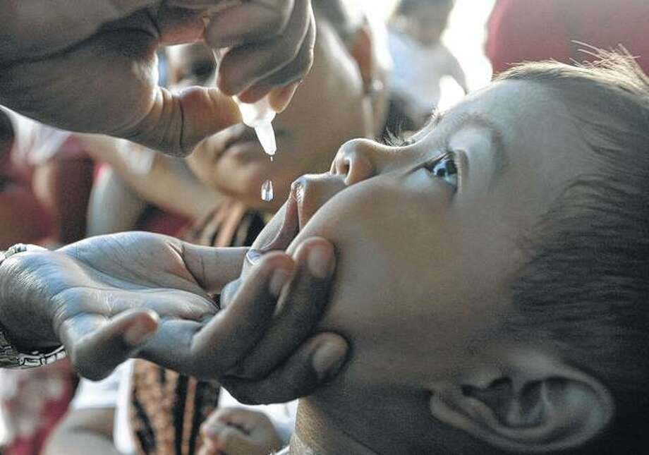 A health worker vaccinates a child against polio. Photo: Dimas Ardian | Getty Images