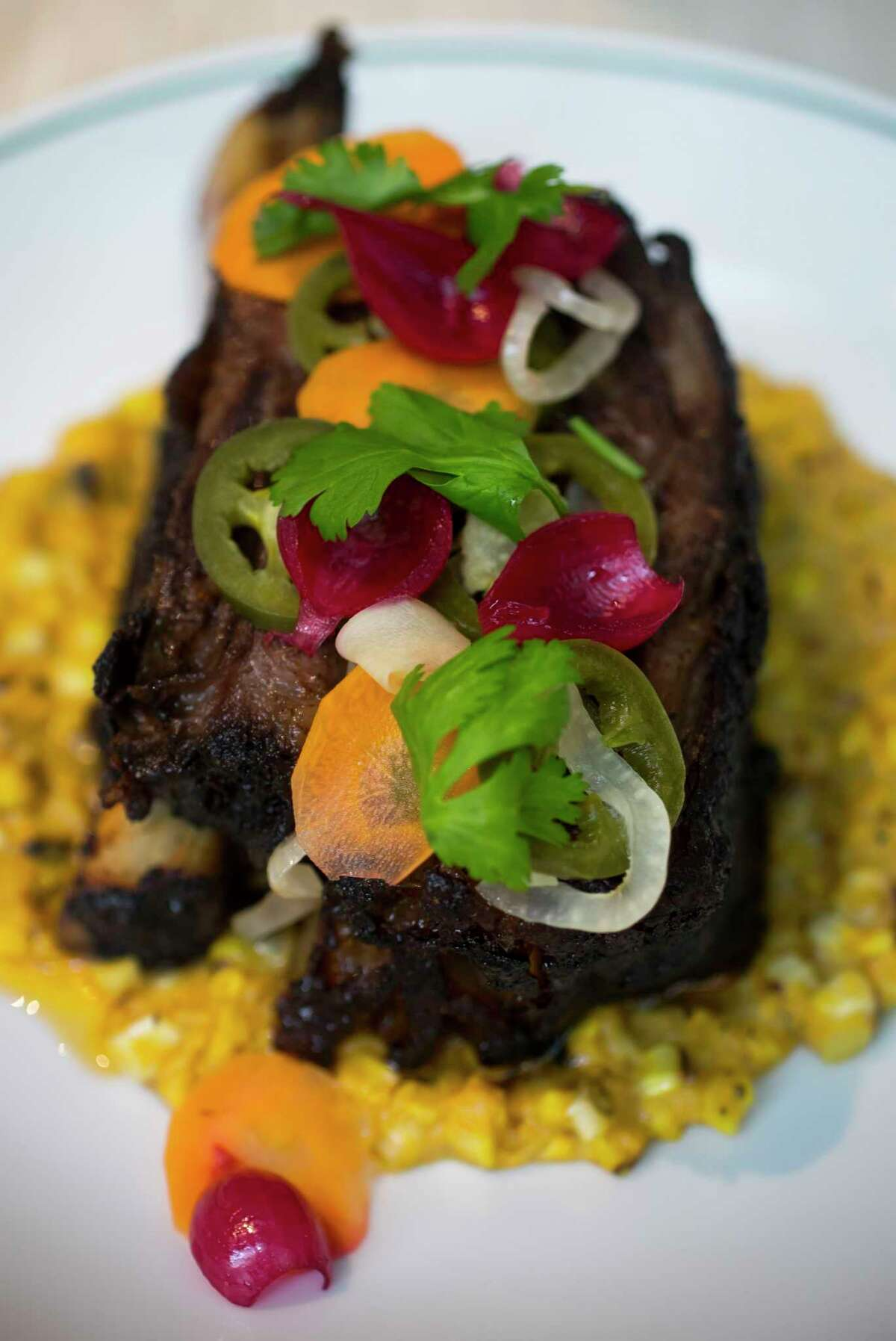 A smoked Wagyu short rib with grilled creamed corn and pickled vegetables at TRIBUTE, the new restaurant at the Houstonian Hotel, Club & Spa.