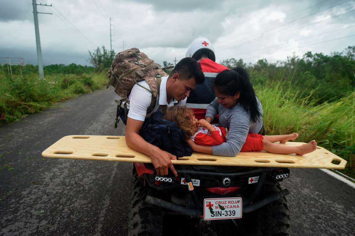An injured girl and her parents are transported on a quad after the motorcycle in which they where travelling squidded off the route linking Escuinapa and the fishing village of Teacapan, which remains cut off after the passage of Hurricane Willa, in Sinaloa state, Mexico on October 24, 2018. - Hurricane Willa crashed ashore in western Mexico Tuesday, lashing the Pacific coast with powerful winds and heavy rain before weakening to a tropical depression as it moved inland.