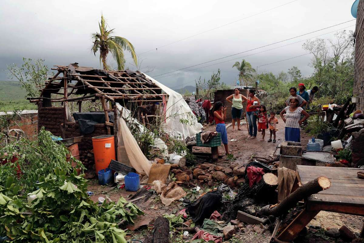 A family stands near their damaged home and debris in the aftermath of Hurricane Willa, in Escuinapa, Mexico, Wednesday, Oct. 24, 2018. Emergency workers on Wednesday were struggling to reach beach towns left incommunicado by a blow from Willa.