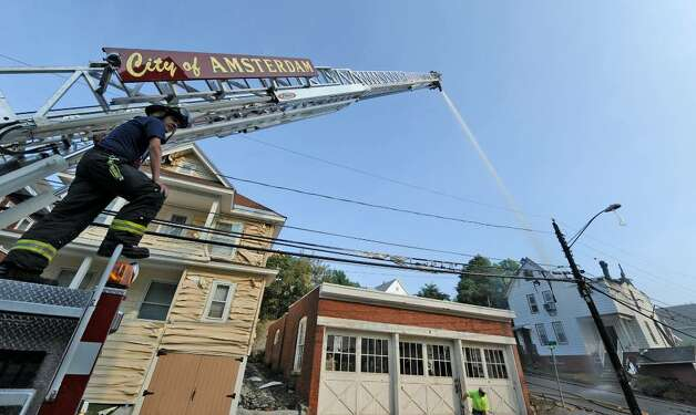 Firefighters battle a blaze Thursday morning that began late Wednesday night. The fire consumed a warehouse and two houses across the street on Brookside Avenue in Amsterdam.  (Skip Dickstein / Times Union) Photo: Skip Dickstein