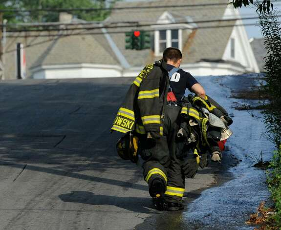 A firefighter carries gear Thursday from the fire scene on Brookside Avenue in Amsterdam.  (Skip Dickstein / Times Union) Photo: Skip Dickstein