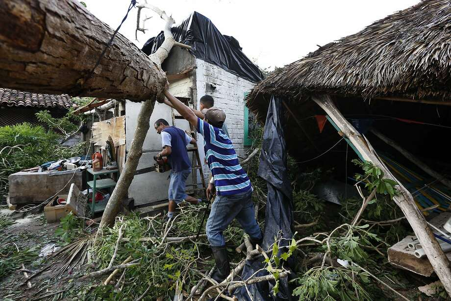A resident works to remove a felled tree in the aftermath of Hurricane Willa in Escuinapa, Mexico. The storm continued to force evacuations due to fear of flooding. Photo: Marco Ugarte / Associated Press