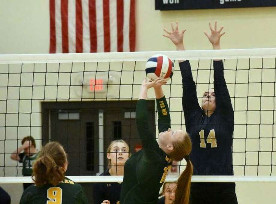Metro-East Lutheran setter Sidney Vetter puts up a pass with Father McGivney middle Madison Webb going up for a potential block during an Oct. 11 match at FMCHS. Photo: Matt Kamp/Intelligencer