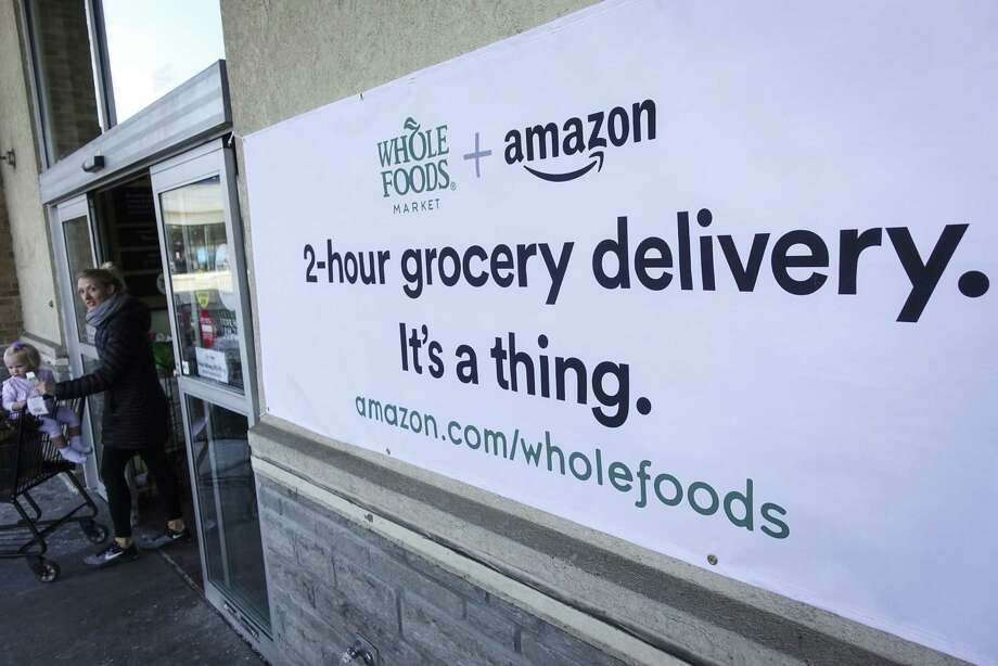 Signage in February 2018 promoting Amazon's Whole Foods delivery service. (AP Photo/John Minchillo, File) Photo: John Minchillo / Associated Press / AP