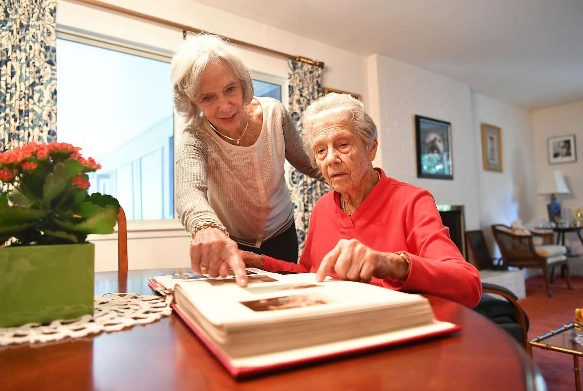Joanne DePuy (L) and Dorothy Tchelistcheff (R) look at photos in a scrapbook in Napa, California on October 12, 2018.