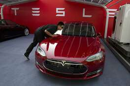 FILE - In this April 22, 2014, file photo, a worker cleans a Tesla Model S sedan before an event to deliver the first set of cars to customers in Beijing. U.S. auto companies such as General Motors, Tesla and Ford faltered this year in Consumer Reports' reliability rankings as readers reported more mechanical trouble and fewer problems with infotainment systems. (AP Photo/Ng Han Guan, File)