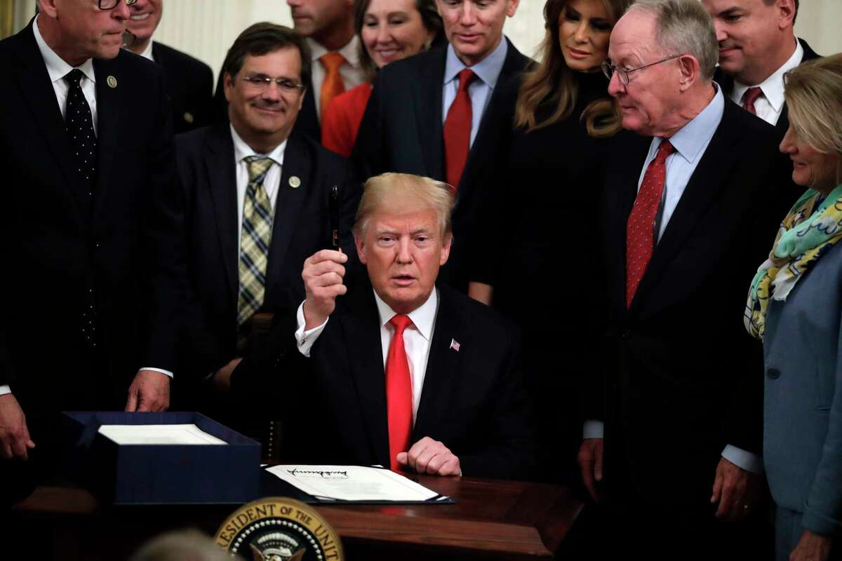 President Donald Trump holds a pen up after signing bipartisan legislation to confront the opioid crisis in the East Room of the White House, Wednesday, Oct. 24, 2018, in Washington.