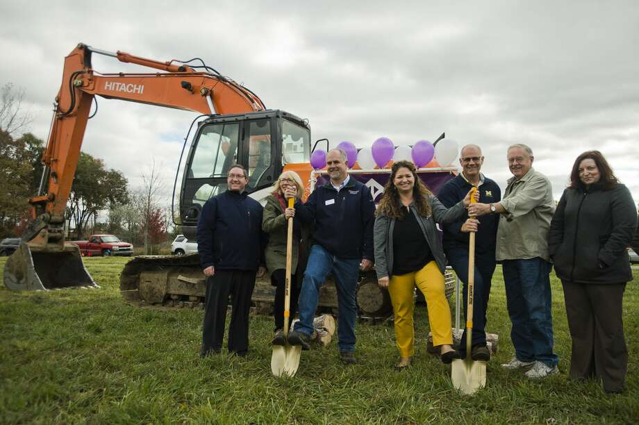 Midland's Open Door Executive Director Renee Pettinger, fourth from right, Greystone Homes owner Kelly Wall, third from left, and others pose for a photo during a groundbreaking for a home being built by Greystone Homes, the proceeds of which will be donated to Midland's Open Door once the home is sold, on Wednesday, Oct. 24, 2018 in Midland. (Katy Kildee/kkildee@mdn.net) Photo: (Katy Kildee/kkildee@mdn.net)