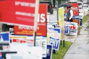 A man walks past campaign signs as people brave the rain to head to the polls for the second day of early voting at the Trini Mendenhall Community Center Tuesday Oct. 23, 2018 in Houston.