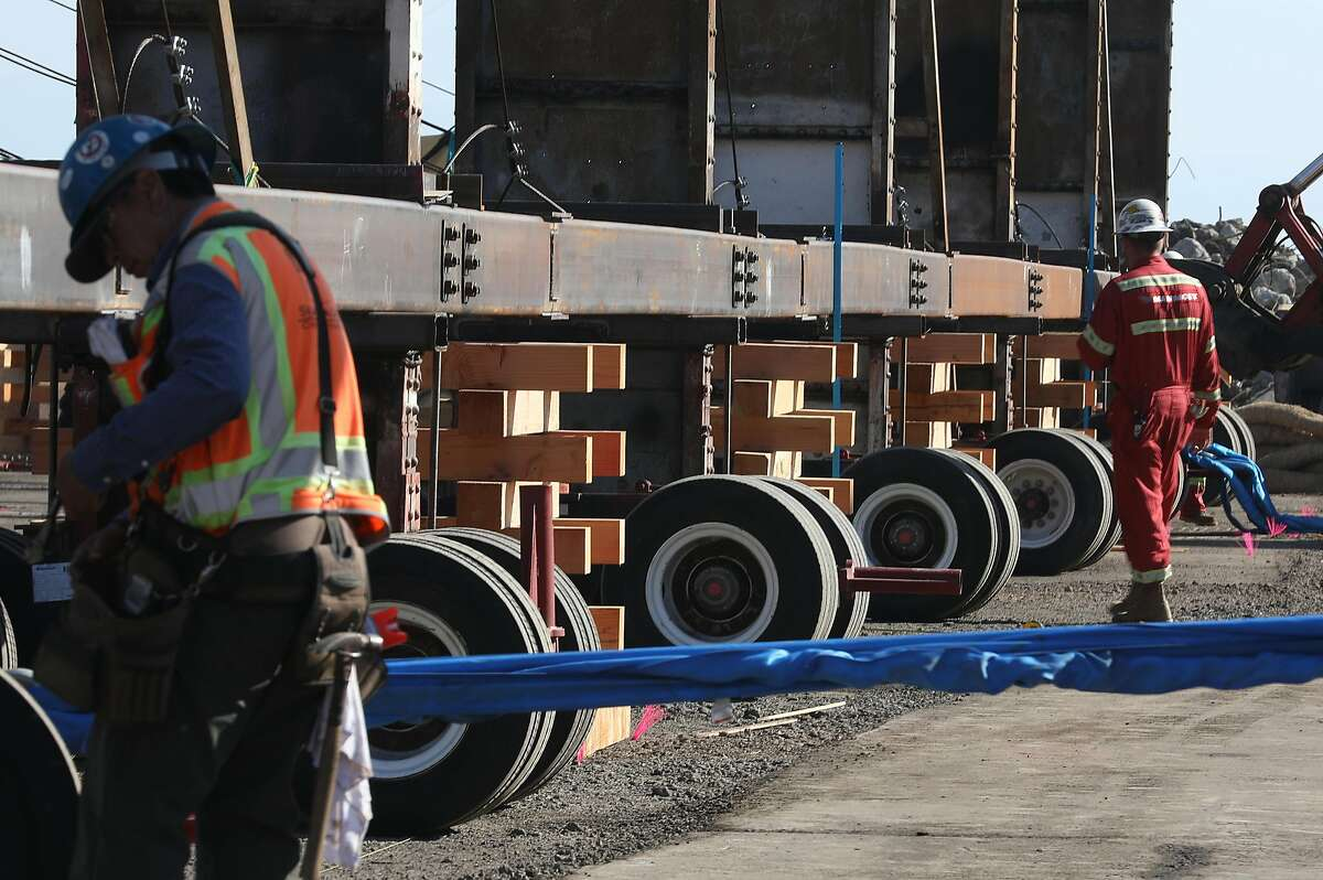 A 153 ton building frame is placed on stands before carriers are removed at a historic shipyard property in Wednesday, Oct. 24, 2018 in San Francisco, Calif.