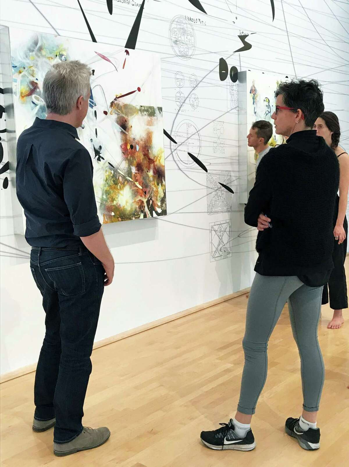 """Moody Center artist-in-residence Matthew Ritchie, left, explains one of the paintings of his installation """"Demon in the Diagram"""" to choreographer Hope Mohr and her dancers, as they collaborate on a performance."""