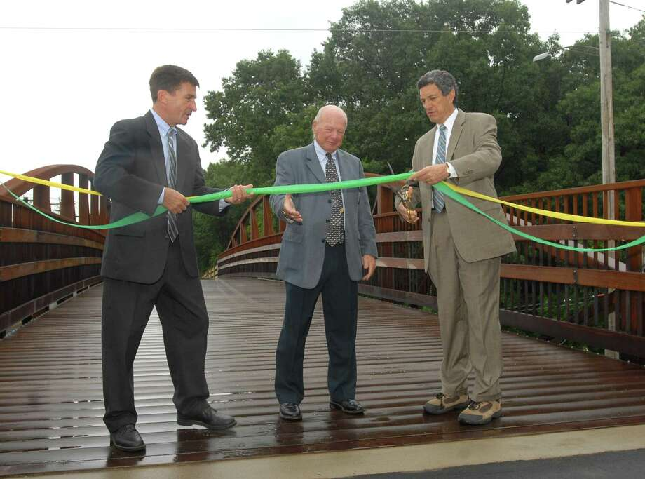 Brad Horrigan | New Haven Register. BH0367. Hamden, Connecticut - 06.18.09: Hamden Mayor Craig Henrici and Connecticut State Sen. Joseph J. Crisco hold the ribbon as David Schaefer, chairman of the Farmington Canal Greenway Commission in Hamden, cuts it. The Hamden portion of the Farmington Canal Greenway is now complete.