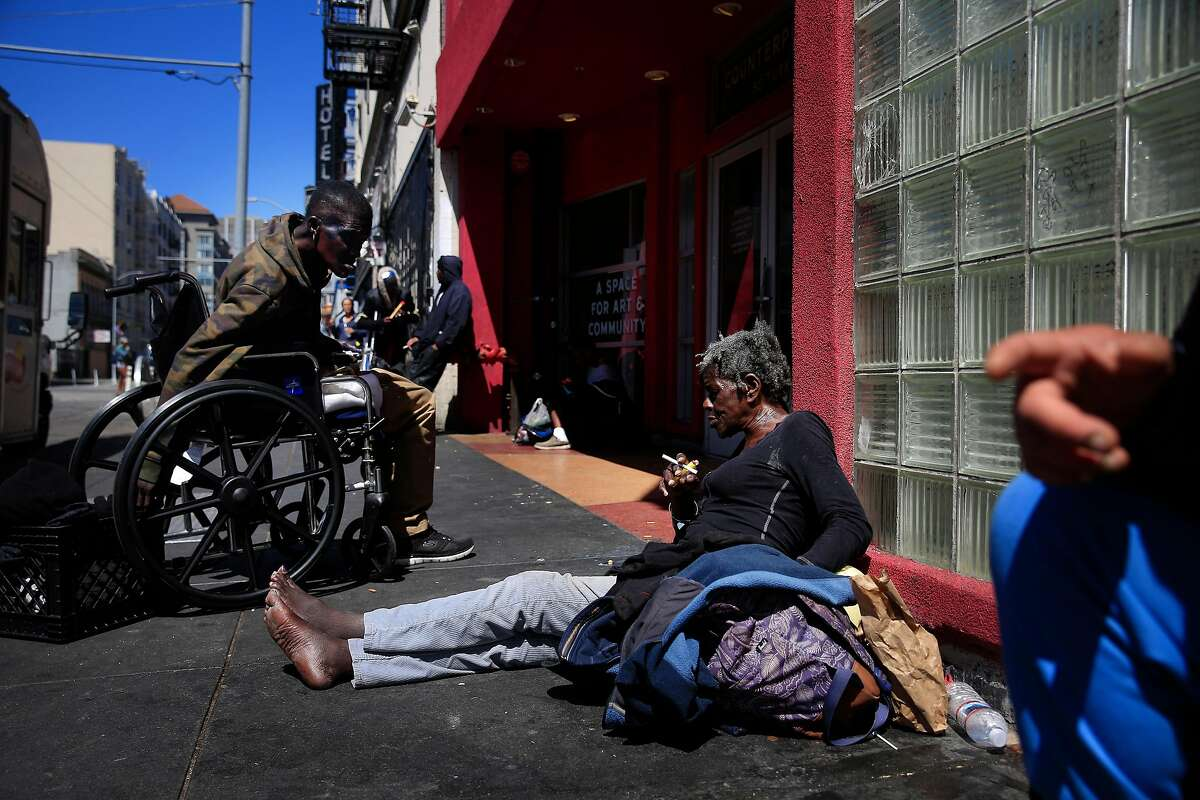 Lauretta Jones (l to r) encourages her friend Deborah Vest to get out of the sun and into the shade as they sit on Turk Street on Wednesday, June 13, 2018 in San Francisco, Calif. Vest says she is currently dealing with homelessness but is on a waiting list to get housing. Jones says she has gotten housing after dealing with homelessness for a couple of months.
