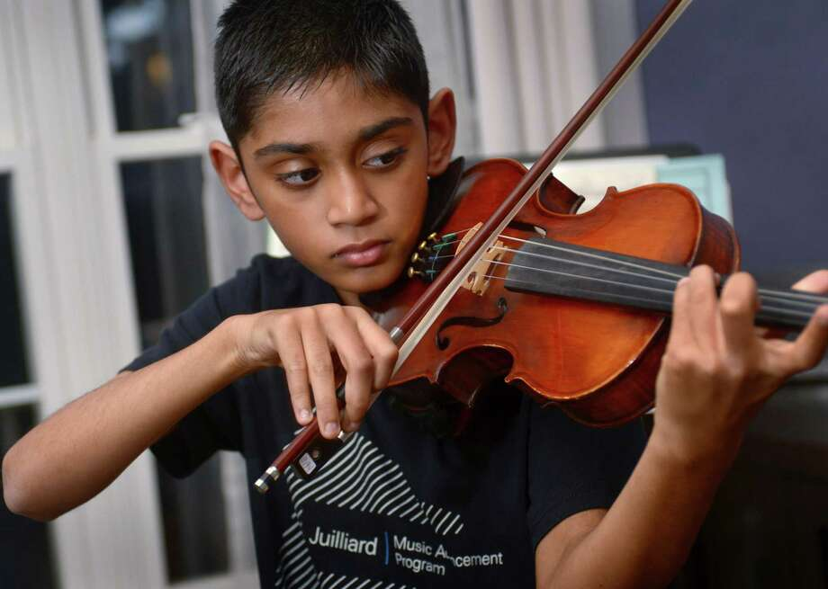 Arav Amin practices violin in the dining room of his home Tuesday in Norwalk. Amin, a Roton Middle School sixth-grader, attends the Juilliard Music Advancement Program with other top musicians aged 8-17. Photo: Erik Trautmann / Hearst Connecticut Media / Norwalk Hour