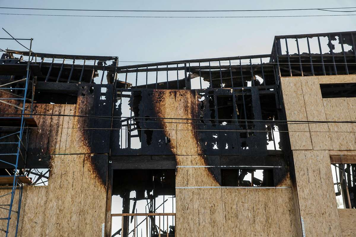 The remnants of a charred building is seen after a massive blaze destroyed six apartment buildings in different phases of construction near West Grand Avenue and Filbert Street in Oakland on Wednesday, Oct. 24, 2018.