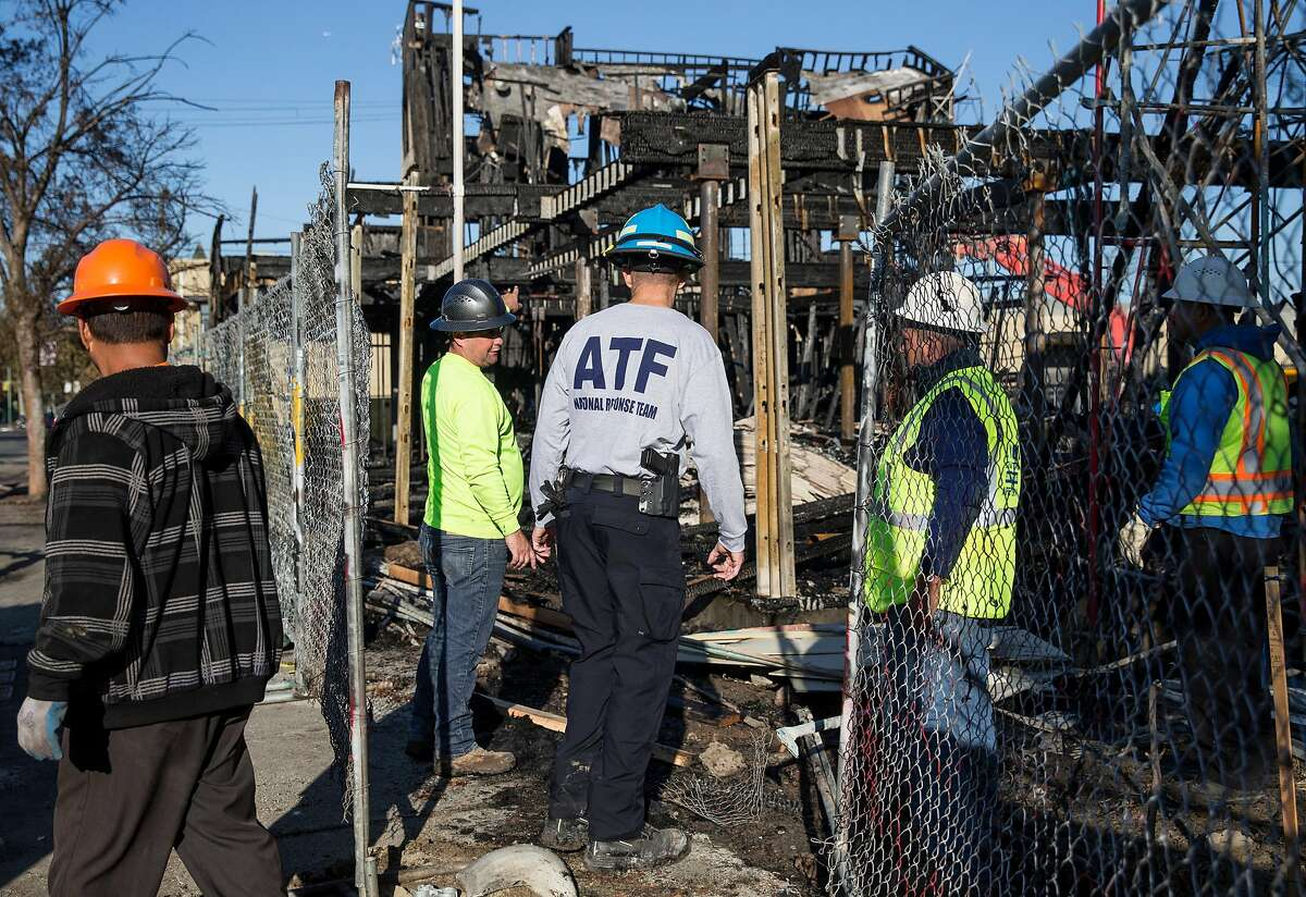 ATF agent Brian Parker, center, walks with local construction workers as he assess the scene where a massive blaze destroyed six apartment buildings in different phases of construction near West Grand Avenue and Filbert Street in Oakland on Wednesday, Oct. 24, 2018.