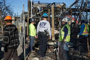 ATF agent Brian Parker, center, walks with local construction workers as he asseses the scene where a massive blaze destroyed six apartment buildings in different phases of construction near West Grand Avenue and Filbert Street in Oakland, Calif. Wednesday, Oct. 24, 2018.