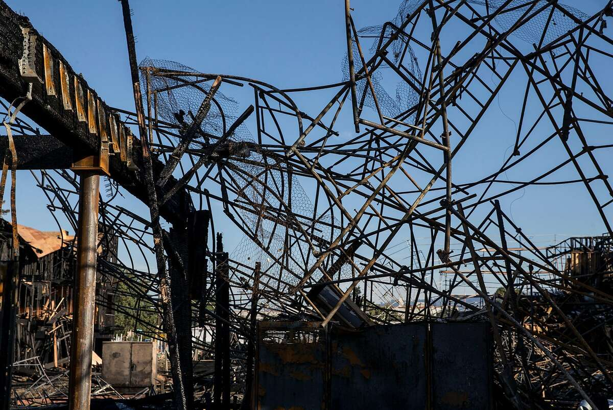 Twisted metal ladders hover over charred building remains after a massive blaze destroyed six apartment buildings in different phases of construction near West Grand Avenue and Filbert Street in Oakland on Wednesday, Oct. 24, 2018.