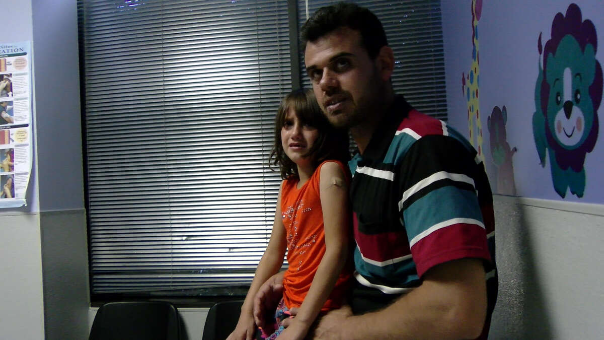 Youssof al-Mosleh and one of his daughters waiting for treatment at Houston's Hope Clinic.