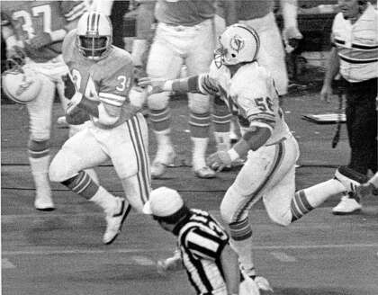 3bc3bbf5d10 Oilers running back Earl Campbell (34) takes a glance at Dolphins  linebacker Steve Towle (56) on the way to his fourth touchdown during his  team's 35-30 ...