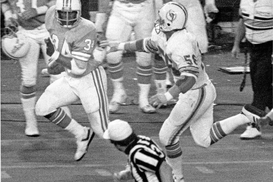 PHOTO FILED: EARL CAMPBELL. 11/20/1978 -- MONDAY NIGHT FOOTBALL - Miami Dolphins at the Houston Oilers. Oilers Earl Campbell's 81-yard TD run in fourth quarter at the Houston Astrodome. Campbell (34) takes a glance at Dolphins linebacker Steve Towle (56) on the way to his fourth touchdown in 35-30 Oilers victory. George Honeycutt / Houston Chronicle HOUCHRON CAPTION (11/21/1978): Earl Campbell, the Tyler Rose, ended his most glorious game as a professional with this 81-yard burst through the Miami Dolphins' defense. From right to left, Campbell takes a pitch, avoids safety Tim Foley and heads around right end. He picks his way through a host of Dolphins, then takes a glance at linebacker Steve Towle (56) on the way to his fourth touchdown in 35-30 victory.