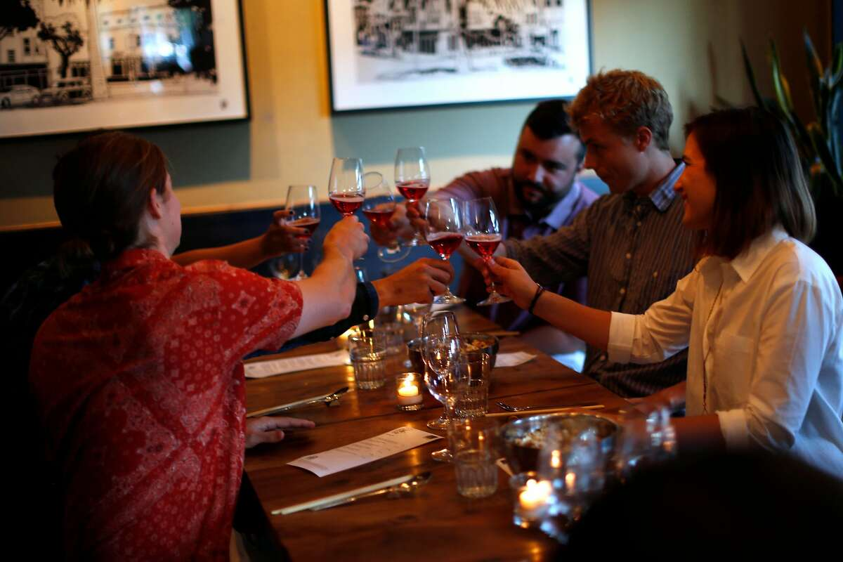 Diners toast glasses of rose as Pink Zebra and Kermit Lynch are hosting an all-rose pop-up dinner at Namu Gaji in San Francisco, Calif., on Monday, Aug. 31, 2015.