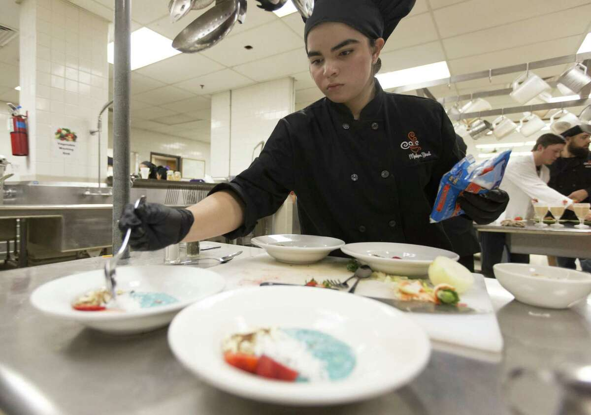 Madison High School culinary arts studentSara Fernandez puts the finishing touches on a dish Wednesday, Oct. 24, 2018 at Madison High School during a cooking competition held to promote Amazon's recent 100 grants to fund offering school breakfast in classrooms.