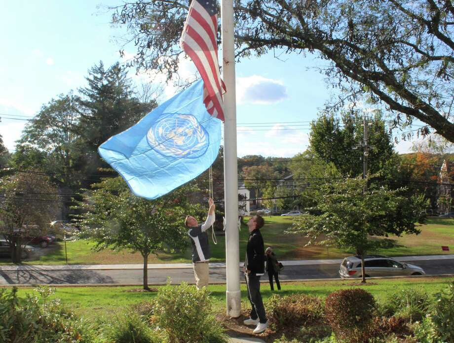Town Hall employee Justin Schaffer and Staples High School senior Taylor Barr raise the United Nations flag outside of Westport Town Hall on Oct. 24. Photo: Sophie Vaughan / Hearst Connecticut Media / Westport News