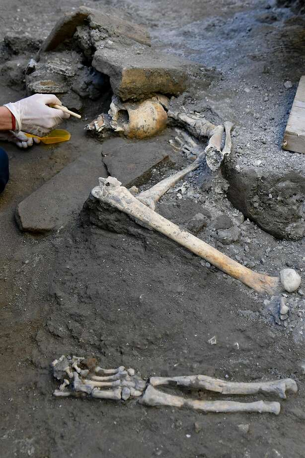 An archaeologist inspects skeletons in the Pompeii archaeological site, Italy, Wednesday, Oct. 24, 2018. The Italian news agency ANSA says new excavations in the ancient buried city of Pompeii have yielded the undisturbed skeletons of people who had taken refuge from the eruption of Mount Vesuvius in A.D.79. The director of the Pompeii archaeological site, Massimo Osanna, told ANSA on Wednesday the skeletons, believed to be two women and three children, were still intact, having been left undisturbed despite looting at the site centuries ago. Photo: Ciro Fusco, Associated Press