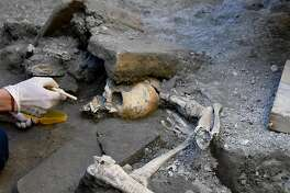 An archaeologist inspects skeletons in the Pompeii archaeological site, Italy, Wednesday, Oct. 24, 2018. The Italian news agency ANSA says new excavations in the ancient buried city of Pompeii have yielded the undisturbed skeletons of people who had taken refuge from the eruption of Mount Vesuvius in A.D.79. The director of the Pompeii archaeological site, Massimo Osanna, told ANSA on Wednesday the skeletons, believed to be two women and three children, were still intact, having been left undisturbed despite looting at the site centuries ago. (Ciro Fusco/ANSA via AP)