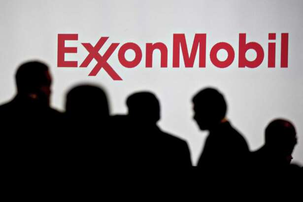 "Attendees stand near Exxon Mobil Corp. signage during a conference in Washington, D.C., on Tuesday, June 26, 2018.The New York Attorney General filed a lawsuit against Exxon Mobil Wednesday, claiming the Texas-based oil giant misled investors about its readiness to tackle the financial challenges of climate change. An Exxon spokesman called the allegations ""baseless"""