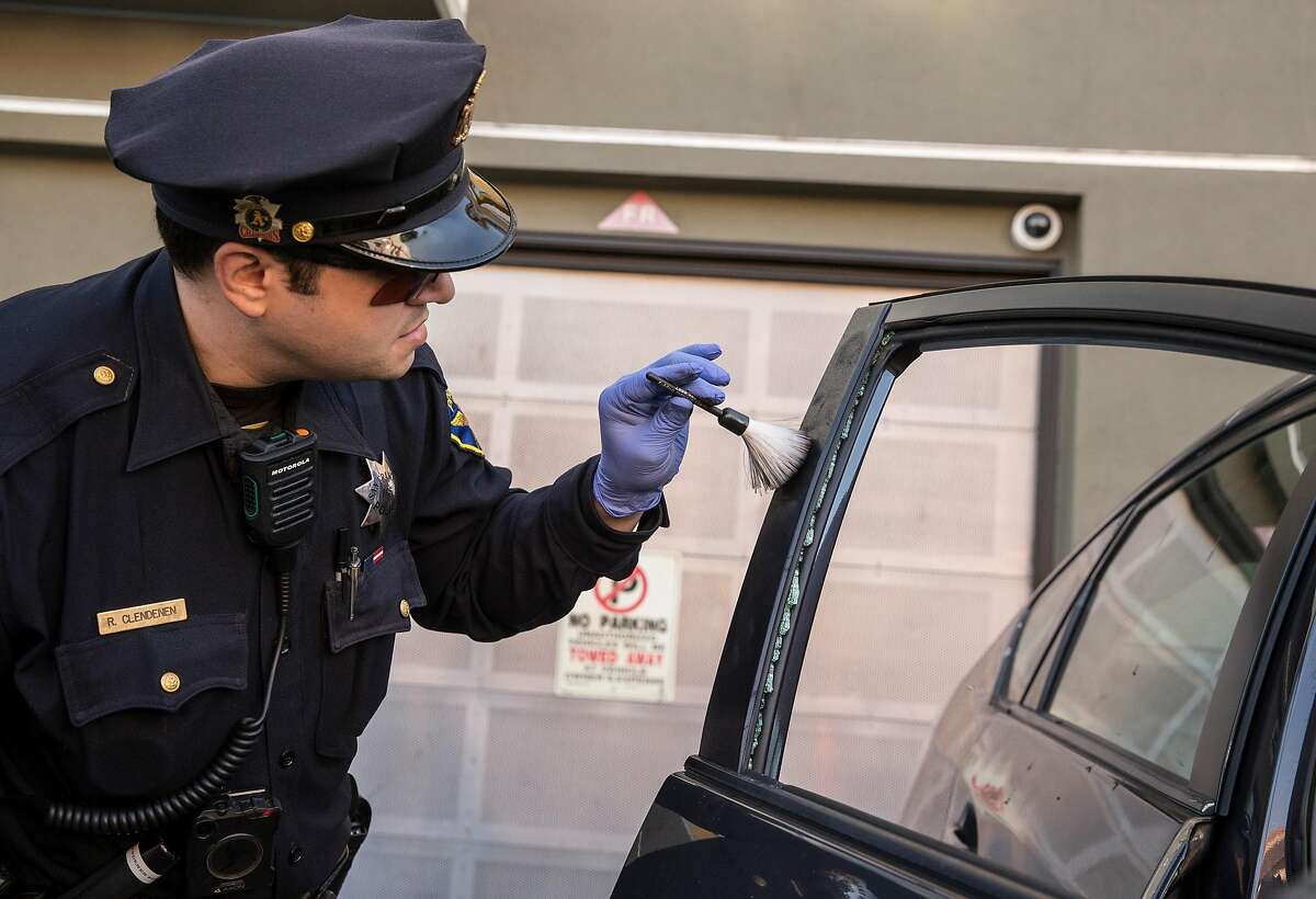 Mission District San Francisco Police Officer Robert Clendenen attempts to lift fingerprints while investigating an auto burglary near Potrero Avenue and 24th Street on Thursday, Feb. 1, 2018 in San Francisco, Calif.