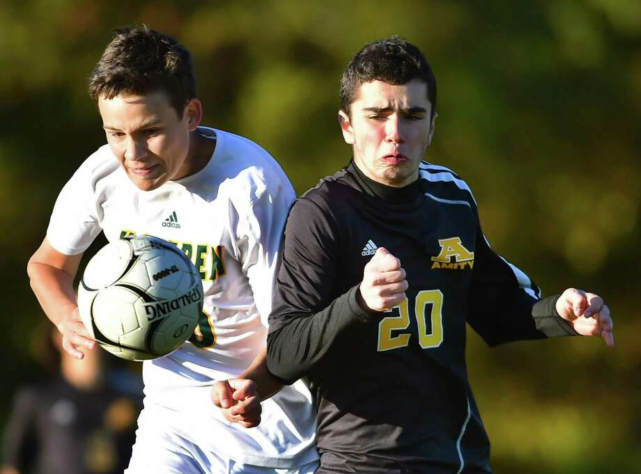 Amity junior forward Ali Bobi battles Hamden senior Andrew Larocque for a loose ball during a SCC contest on Wednesday. Amity won 2-0. Photo: Catherine Avalone / Hearst Connecticut Media / New Haven Register