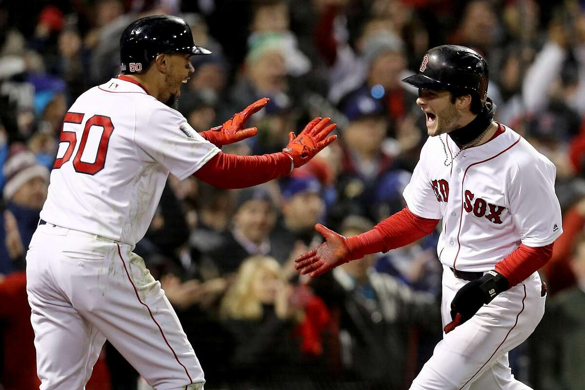 BOSTON, MA - OCTOBER 24: Mookie Betts #50 and Andrew Benintendi #16 of the Boston Red Sox celebrate each scoring a run on a hit by teammate J.D. Martinez (not pictured) during the fifth inning against the Los Angeles Dodgers in Game Two of the 2018 World Series at Fenway Park on October 24, 2018 in Boston, Massachusetts. (Photo by Maddie Meyer/Getty Images)
