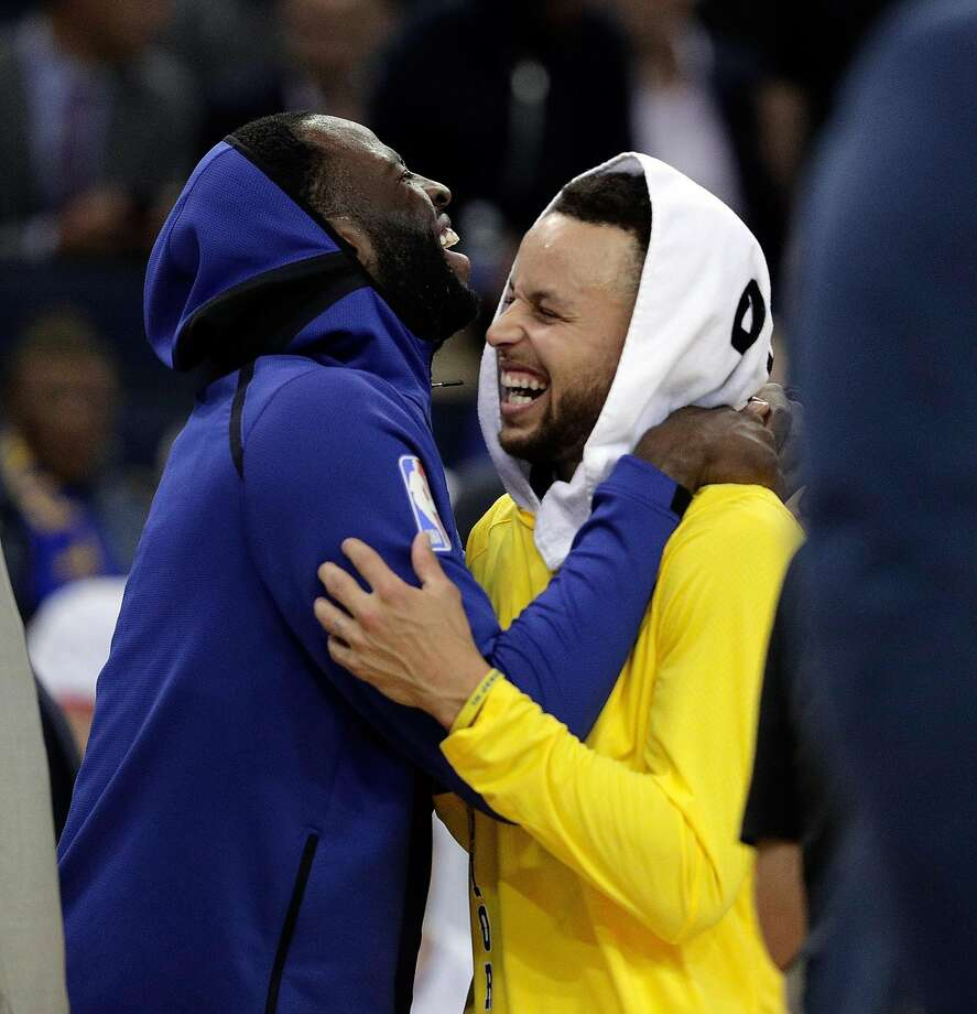 Stephen Curry (30) and Draymond Green (23) laugh during a timeout in the fourth quarter as the Golden State Warriors played the Washington Wizards at Oracle Arena in Oakland, Calif., on Wednesday, October 24, 2018. = Photo: Carlos Avila Gonzalez, The Chronicle