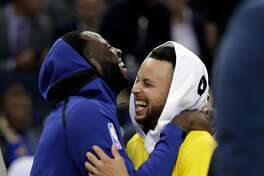 Stephen Curry (30) and Draymond Green (23) laugh during a timeout in the fourth quarter as the Golden State Warriors played the Washington Wizards at Oracle Arena in Oakland, Calif., on Wednesday, October 24, 2018. =