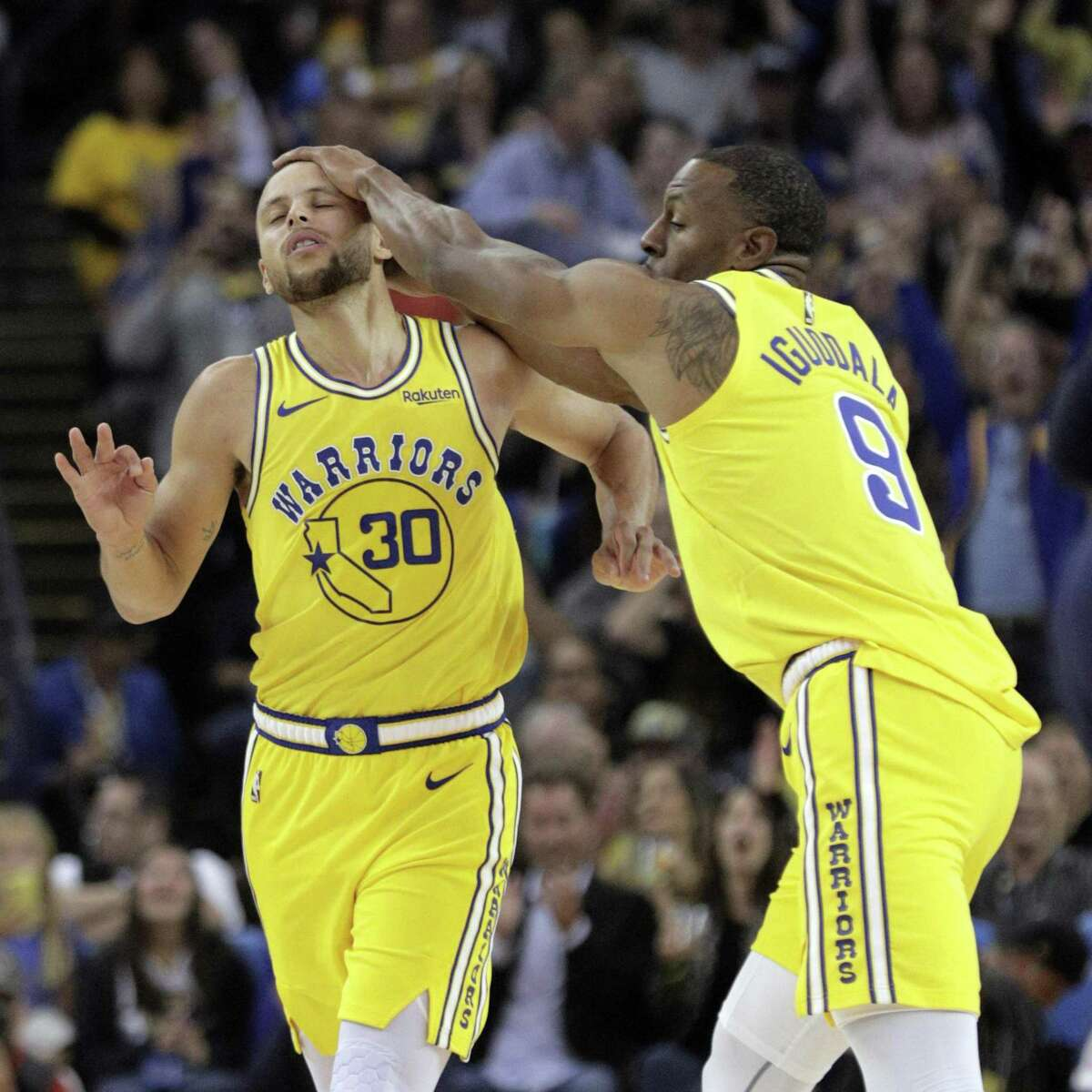 Stephen Curry (30) reacts with Andre Iguodala (9) after hitting a three point shot in the second quarter as the Golden State Warriors played the Washington Wizards at Oracle Arena in Oakland, Calif., on Wednesday, October 24, 2018.