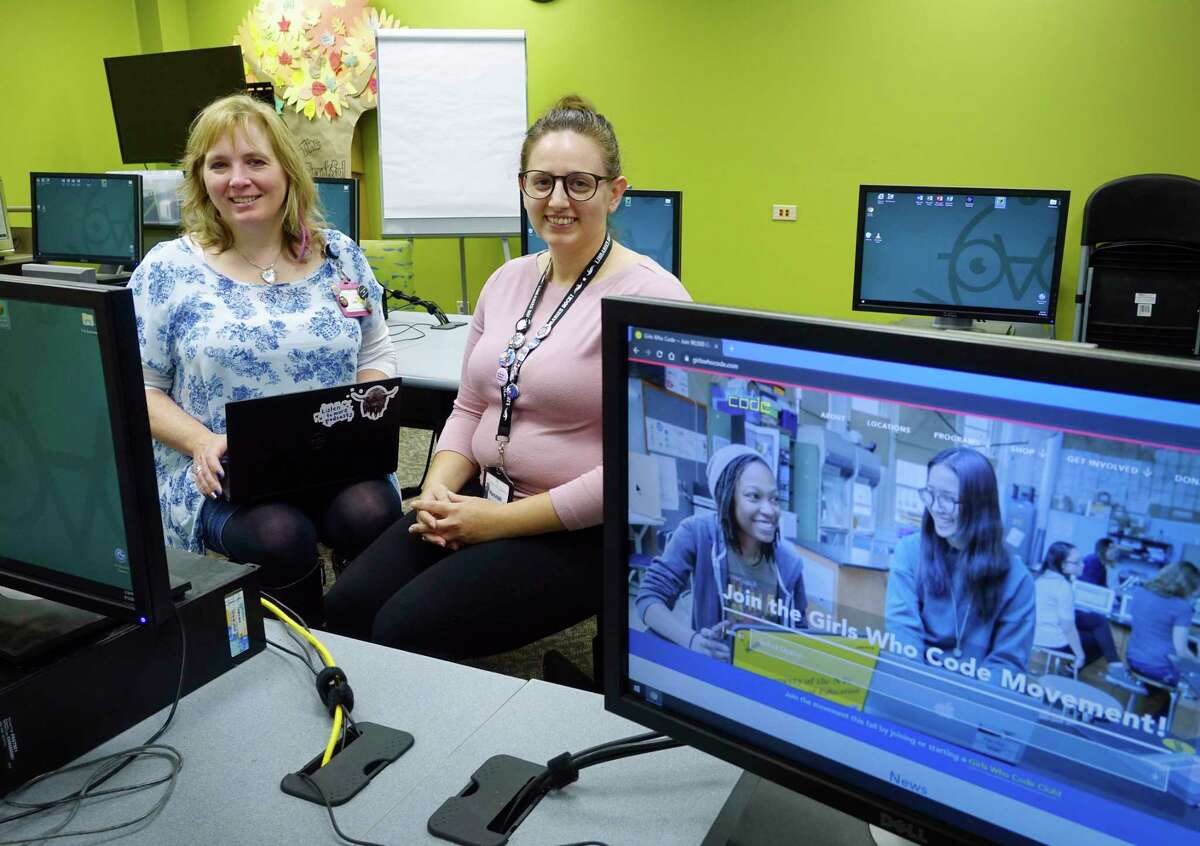 Lisa Newman, left, head of Youth Services for the Albany Public Library, and Hannah Ricottilli, a librarian assistant, pose for a photo in the computer lab at the main branch on Wednesday, Sept. 12, 2018, in Albany, N.Y. The two women are running the Girls Who Code program. The eight-week sessions in the fall and the spring teach coding to girls ages 11 to 17. (Paul Buckowski/Times Union)