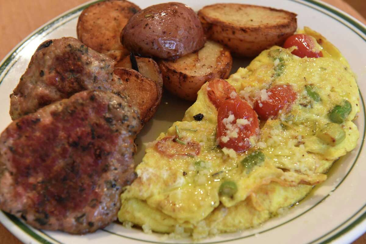 Tuscan omelette - three farm fresh eggs filled with fresh asparagus, grape tomato, grated parmesan and drizzled house made herb oil, includes breakfast meat and toast at Main Street Goodness, home of Pieconic on Friday, Sept. 21, 2018 in Chatham, N.Y. (Lori Van Buren/Times Union)