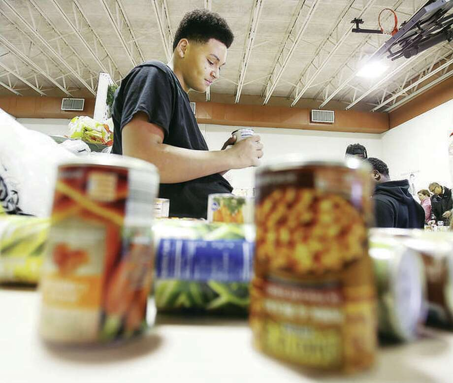 Roxana High School student Kyler Clark-Bowens helps check the expiration dates of canned goods during last year's Community Christmas drive. Photo: John Badman | The Telegraph