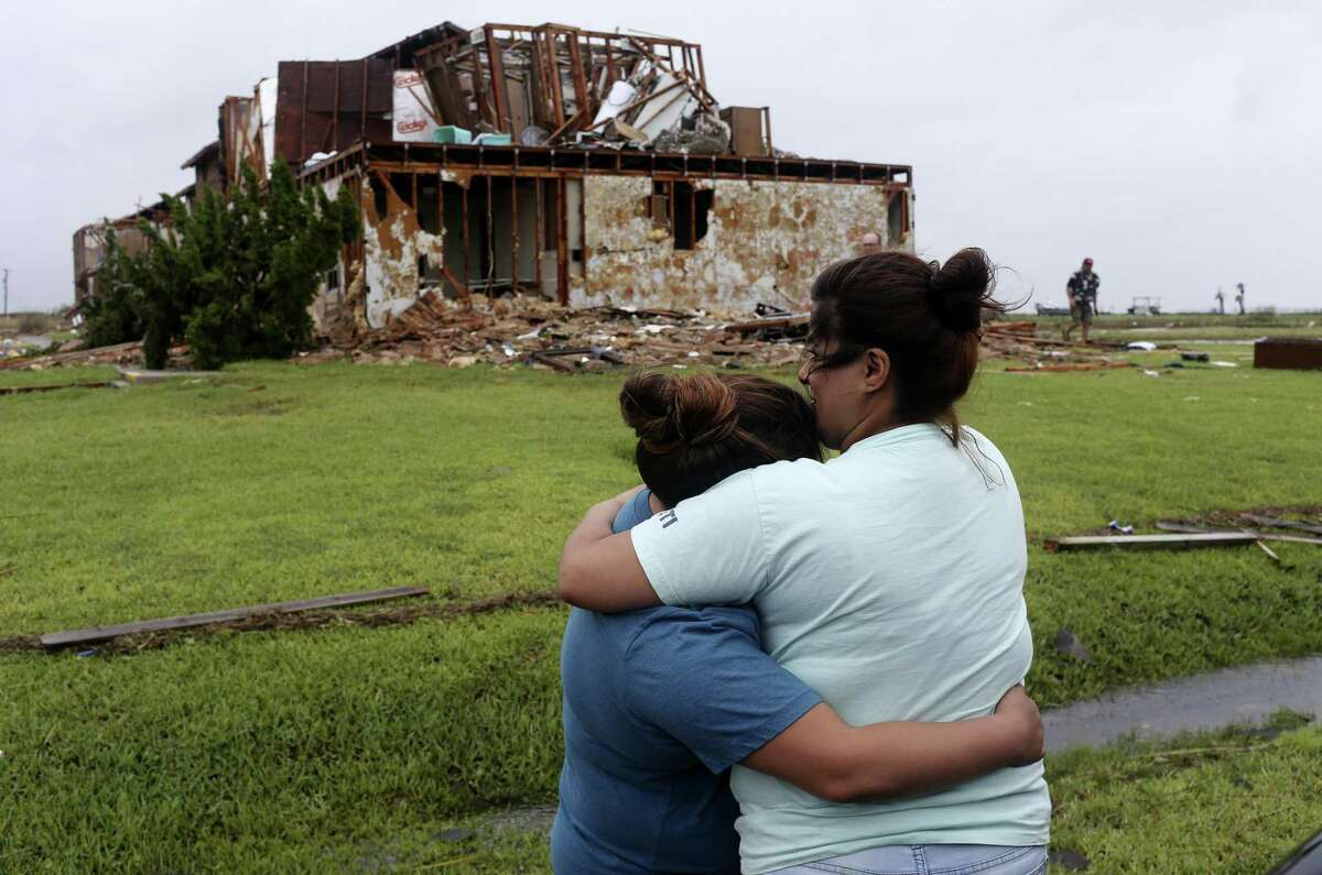 Julie Martinez, 37, right, hugs her daughter, Gabrielle Jackson, 19, by the damaged apartment of her aunt at the Salt Grass Landing Apartments in Rockport, Texas, Monday, August 28, 2017. All the residents of the complex evacuated before Hurricane Harvey made landfall near the area Friday night. The units suffered major damages and residents weren?•t allowed access due to the dangerous conditions.