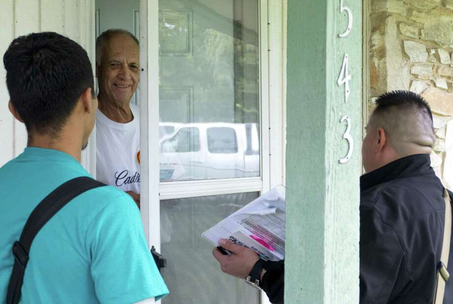 Alan Rivas, right, and Jeremiah Lopez, left, of the Texas Organizing Project, speak with Jacinto Hernandez during a block walk to inform voters about their opposition to Props A and B and their support of some Democratic candidates on Oct. 16. Photo: Billy Calzada /