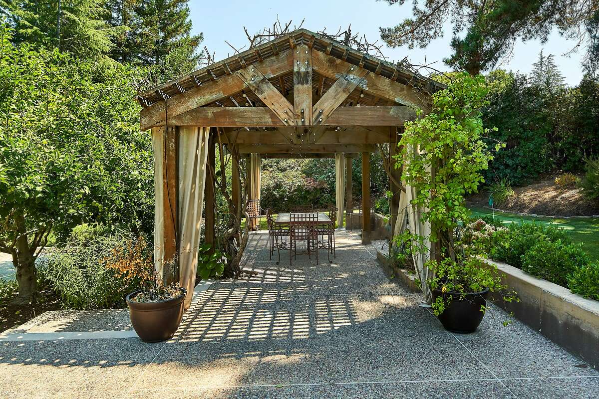 The secluded estate enjoys a wealth of outdoor spaces, like this sheltered patio and putting green.
