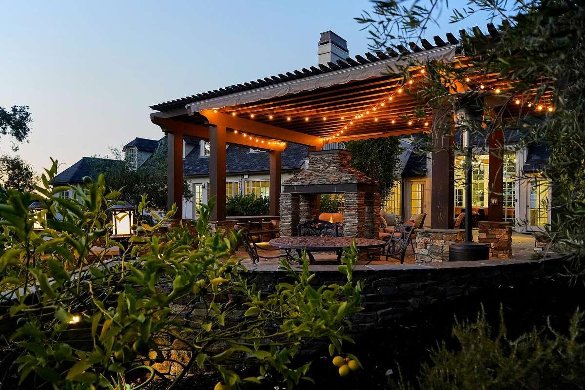 A pergola patio behind the main home offers a two-sided fireplace.