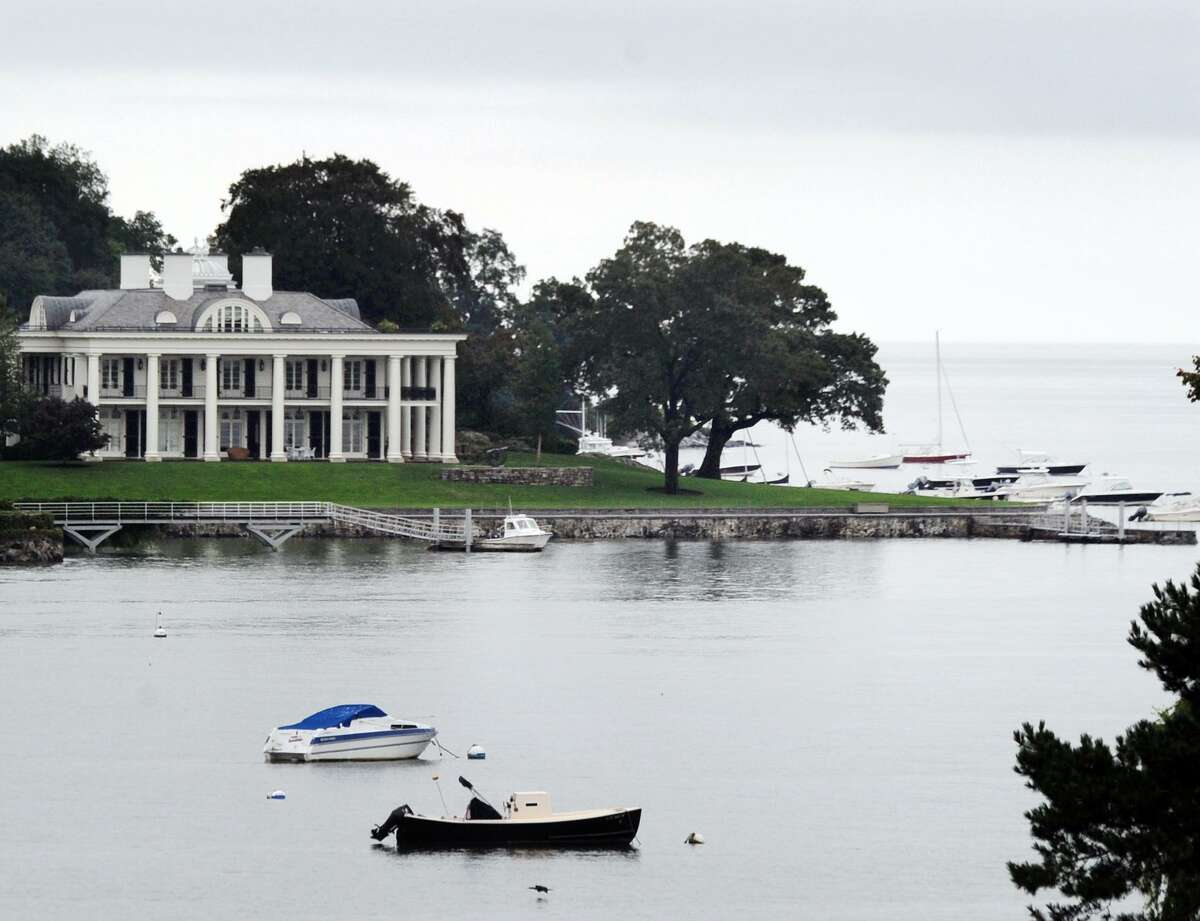 With the Paul Tudor Jones mansion visible in the backgound, boats can be seen moored in Byram Harbor off the coast of Greenwich, Conn., Tuesday, Sept. 11, 2018. With hurricane Florence, a category 4 storm with sustained winds of 130 mph, approaching the east coast of the United States in the area of the Carolinas, the harbormasters in Connecticut are warning boaters that now is the time to prepare and shore-up boats.